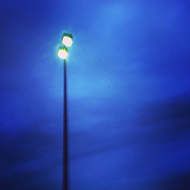 a lamppost is a conversation between you and the blue grey passing of time. verticality is the comfort i often forget. what i want is some company. what i want is light upon light in the paradise/parking lot.